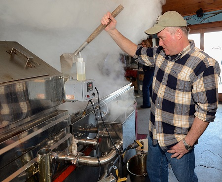 Sam Cutting IV. boiling maple sap into syrup in our sugar house at Dakin Farm.