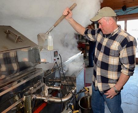 Sam Cutting IV. boiling maple sap into syrup in our sugar house at Dakin Farm.